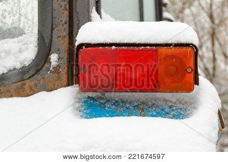Old tractor taillight closeup covered with snow in winter