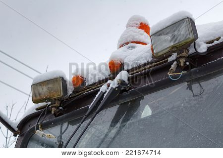 Old tractor secondary headlight with orange warning lamps closeup covered with snow