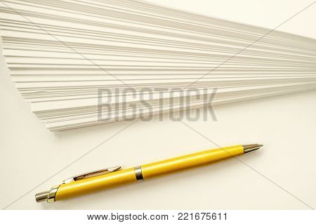 a stack of sheets of white paper and ball point gold pen writing set