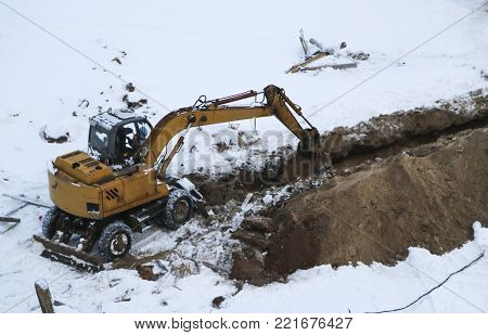 Excavator Digs Frozen Land Covered With Snowdrifts. Preparation Of The Site For Winter Construction.