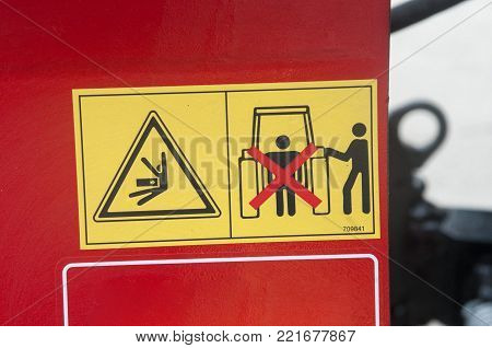 Warning sign on agricultural machinery. Do not stand behind the tractor. It is possible to get a shock. Observe the distance.