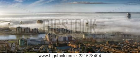 Editorial SWANSEA, UK - JANUARY 01, 2018: An unusual early morning heavy fog or sea mist engulfs the city of Swansea, South Wales, UK with only a few tall buildings showing through.
