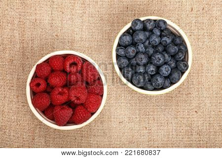 Close up two ceramic bowls of fresh ripe blueberry and red raspberry over linen canvas tablecloth, elevated top view, directly above