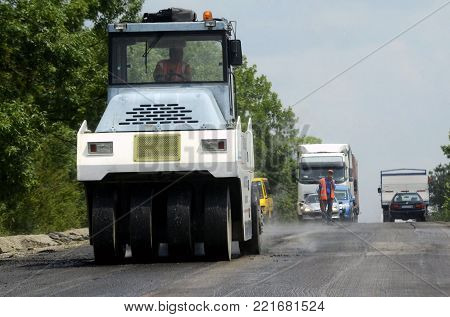 Road roller operating on road under construction