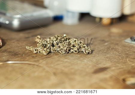 Craft jewelery making with professional tools. Gold chain repairing. Macro shot. Different stages of the manufacturing process of jewelry chain. The elements of a future chain. Selective focus.