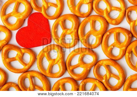 Valentine's day or fod background. Salted fresh pretzels pattern and red heart on white