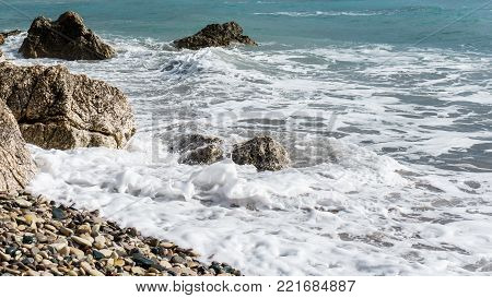 Picture of frothy sea, pebble beach, stones in afternoon