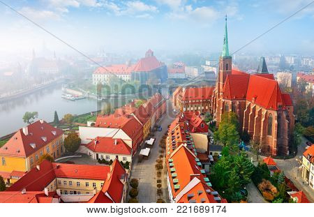 Wroclaw city in Poland top view to sanctuary church with high broach and street old houses. Red roofs. River in mist evening sunset.