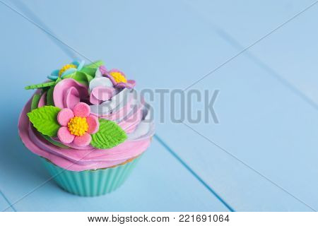 Closeup Cupcake Creamy Multicolored Top With Colorful Flowers And Butterflies On Blue Background
