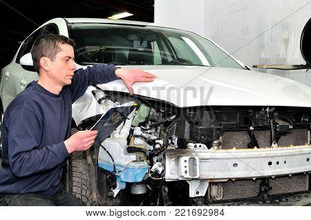 Professional car appraiser evaluate car damage after a crash.