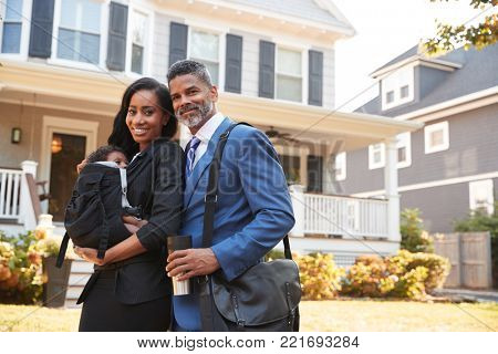 Portrait Of Business Couple With Baby Son Leaving House For Work