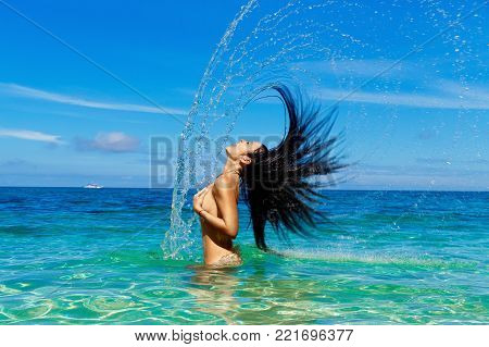 Beautiful brunette resting on a tropical sea. Hair and spray. The concept of summer vacation.