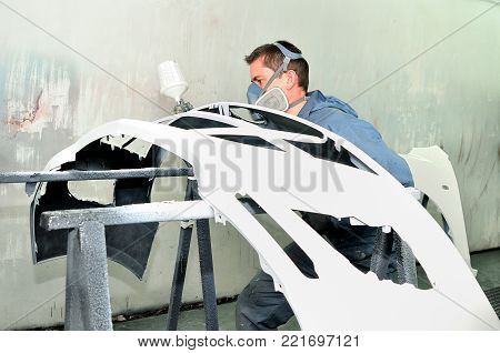 Professional body shop worker painting white car bumper.