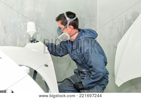 Professional body shop worker painting white car parts.