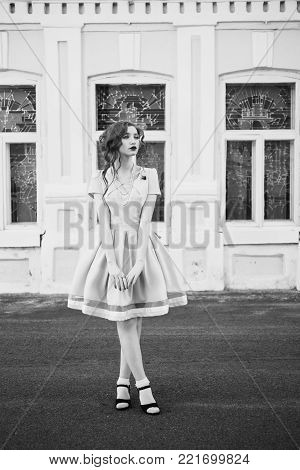 A woman with curly hair in a dress on background vintage window. Black and white art monochrome photography. Black and white creative photography. Black and white conceptual image. Beautiful black and white background. Black and white portrait.