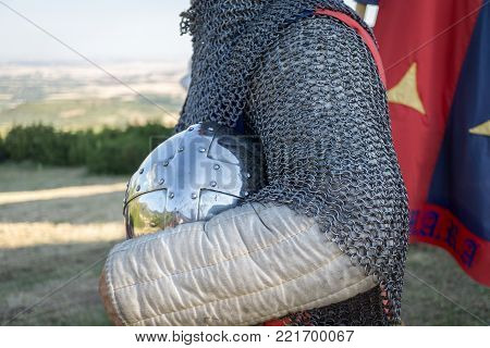 Medieval knight holding his helmet, reenactment with costumed characters and medieval armor with chainmail, helmet. Medieval demonstration and recreation
