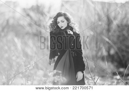Black and white art monochrome photography. Black and white creative photography. Black and white conceptual image. Beautiful black and white background. Black and white portrait. A woman with curly hair in a black coat at the autumn background.