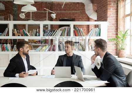 Three businessmen in suits discussing documents or project statistics sitting on executive meeting at conference office table, partners making new business plan, startupper convincing investors