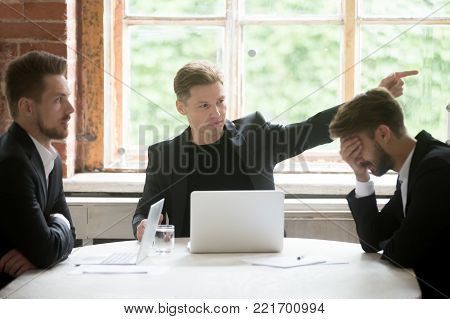 Angry boss firing unprofessional employee with hand gesture at office meeting, dissatisfied ceo dismissing male incompetent manager for poor performance or bad work result sitting at conference table
