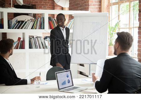 Smiling friendly african american coach giving presentation to businessmen in office, black project manager, happy ceo or team leader working with flipchart at group corporate multiracial meeting