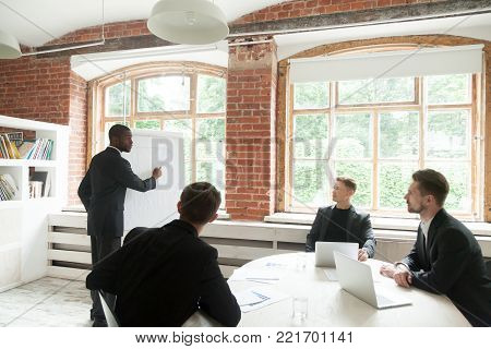 Serious african american speaker gives presentation to businessmen at meeting, executive group listening to ceo working with flipchart explaining new design project idea at corporate office briefing