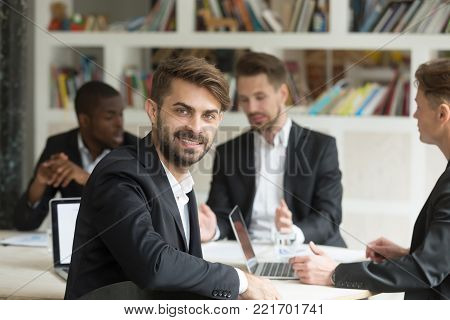 Smiling young team leader wearing suit looking at camera on group corporate office meeting, positive professional company ceo executive, ambitious project manager or entrepreneur, headshot portrait