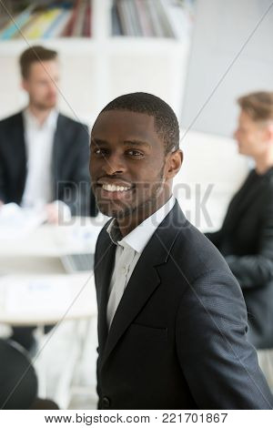 Smiling attractive young african american businessman in suit looking at camera, headshot vertical portrait of black professional executive manager posing with business partners team at background