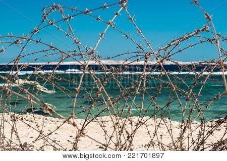 Old barbed wire in front of Red sea in Egypt. Close-up. This photo symbolizes the ban on bathing. Safety fence of barbed wire against the blue sky and sea.