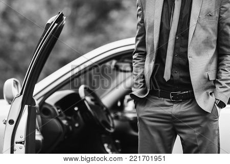 Successful businessman in a dark business suit. Black and white art monochrome photography. Black and white creative photography. Black and white conceptual image. Beautiful black and white background.