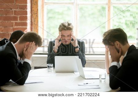 Stressed boss and executive team searching problem solution at meeting, partners holding heads in hands depressed by failure bad news, feeling desperate about company bankruptcy or financial crisis poster