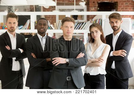 Successful multinational professionals team portrait, multi-ethnic group of confident diverse business people standing looking at camera, company ceo boss and employees posing in office together