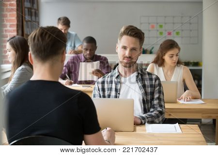 Young businessman looking at camera sitting at desk with laptop, man working in modern cozy co-working space with diverse multiracial people, freelancer in shared office posing at workplace, portrait