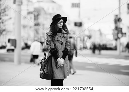 Black and white art monochrome photography. Black and white creative photography. Black and white conceptual image. Beautiful black and white background. Black and white portrait. Woman with curly hair in coat and black round glasses on background of big