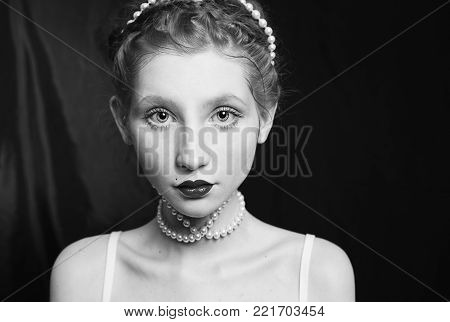 Woman with long hair pinned on her head, a necklace of beads. Black and white art monochrome photography. Black and white creative photography. Black and white conceptual image. Beautiful black and white background. Black and white portrait.