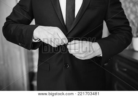 A stylish man in a dark jacket. The businessman in a respectable suit. Black and white art monochrome photography. Black and white creative photography. Black and white conceptual image. Beautiful black and white background.