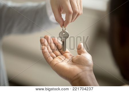 Realtor woman giving african american customer hand taking key, black man buyer house owner purchasing new home, mortgage loan investment contract, buying real estate deal concept, close up view