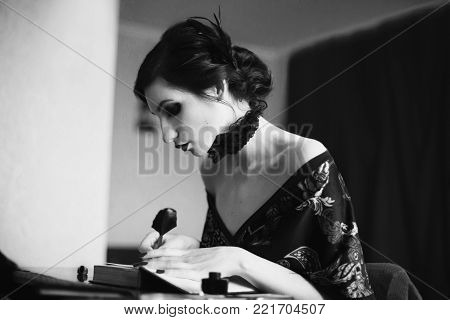 A woman with curly hair in a bathrobe and retro makeup. Black and white art monochrome photography. Black and white creative photography. Black and white conceptual image. Beautiful black and white background. Black and white portrait.