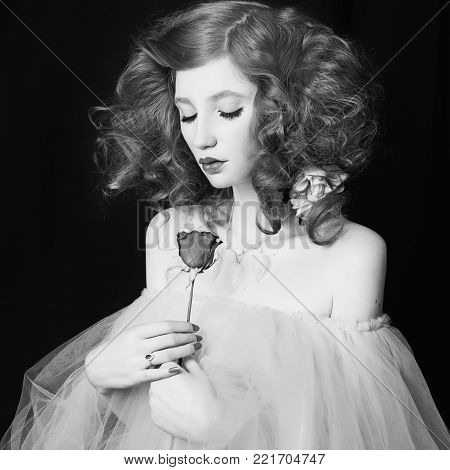 Girl with pale skin with a rose in hands on a black background. Black and white art monochrome photography. Black and white creative photography. Black and white conceptual image. Beautiful black and white background. Black and white portrait.