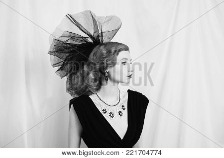 Woman with unusual appearance in black dress and veil. Black and white art monochrome photography. Black and white creative photography. Black and white conceptual image. Beautiful black and white background. Black and white portrait.
