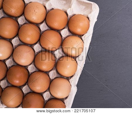 yellow raw eggs in eggshell on paper tray, top view, empty space on the right