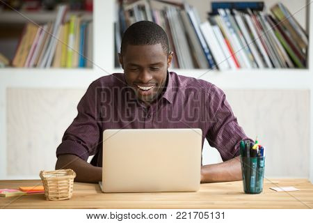 Smiling african-american man using laptop sitting at home office desk, happy excited black e business owner looking at computer screen pleased by reading good news, chatting in social network