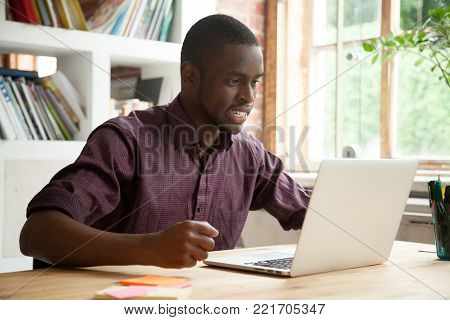 African businessman looking at laptop screen frustrated by bad news, stressed man in tension cheering sport team watching match online, black trader nervous angry about stock trading market crisis