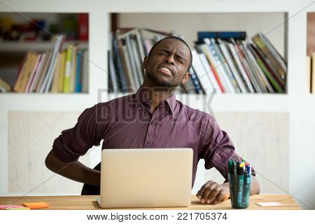African-american man touching back sitting at desk feeling sudden backache, black businessman suffering from low-back lumbar pain after sedentary work at laptop computer, incorrect posture problems
