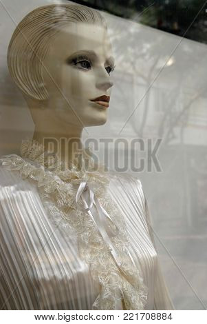 Mannequin woman, dressed in a white blouse in the shop window, glints on the glass.