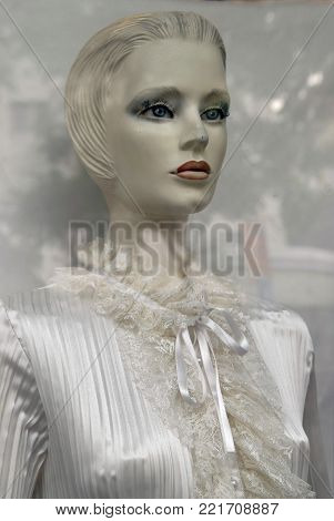 White woman holding a mannequin in a white dress behind a glass shop.