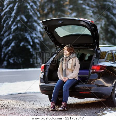 Young woman ready to go on vacations-single or with her boyfriend-and relaxing in the opened trunk of a car before a road trip. Winter automobile travel in the countryside. Alps, Bavaria, Germany