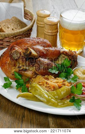 Pork knuckle and beer on wooden table in Bavarian style