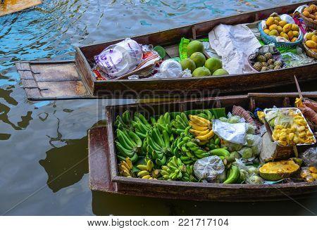 Bangkok, Thailand - Jun 19, 2017. Selling fruits on boat at Damnoen Saduak Floating Market in Bangkok, Thailand. Damnoen Saduak is Thailand most popular floating market.