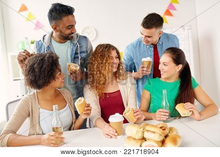 corporate, celebration and people concept - happy friends or team eating sandwiches with coffee and non-alcoholic drinks at office party
