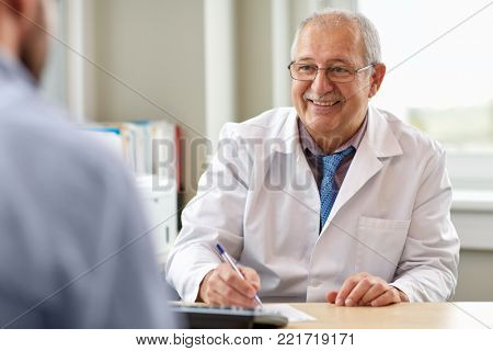 medicine, healthcare and people concept - happy smiling senior doctor with prescription talking to young male patient at hospital